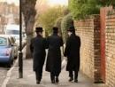 Man behind warning public sign depicting Orthodox Jewish man apologises